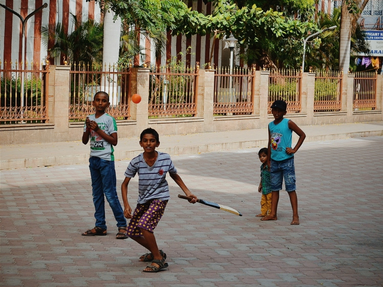Kids playing cricket by the temple